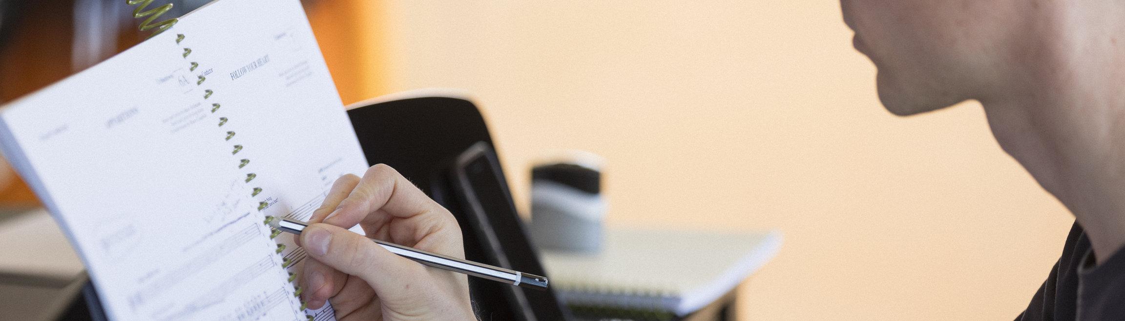 En person sitter med penna i handen och skriver i ett block.