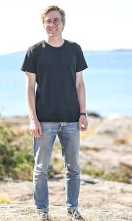 Läraren står på klippan med havet bakom